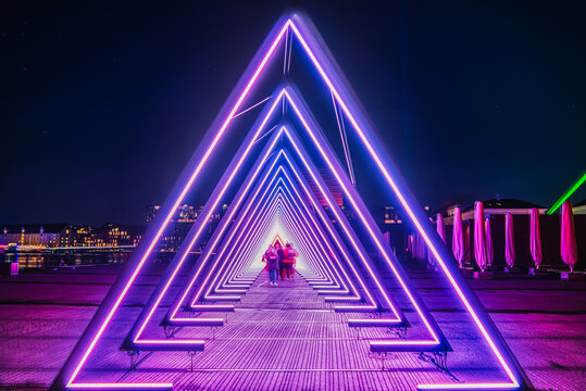 Purple coloured gate of light or purple light tunnel installation made of triangular neon and led lights at night as blurred people walk through the bright deep passage that resembles a human trachea
