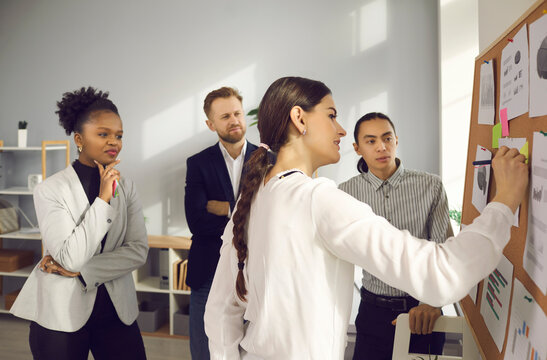 Professional team of multiracial business people brainstorming in office. Young woman writing idea on sticky note pinned to bulletin board in group meeting with multiethnic coworkers. Teamwork concept