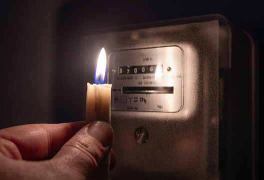 A person's hand with candle in complete darkness looking on electricity meter at home. Power outage, blackout concept.