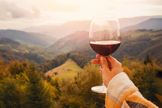 Woman's hand holding a glass of red wine with a mountain view.