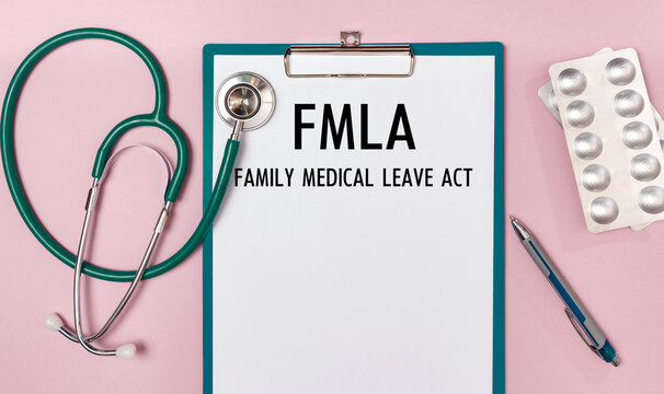 Worksheet with the inscription Family Medical Leave Act - FMLA , stethoscope and pills