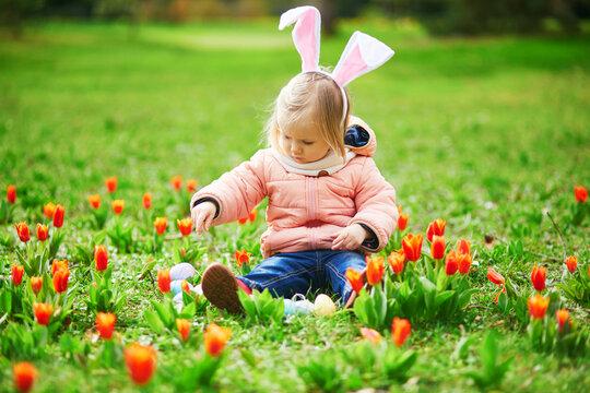 Cute little girl playing egg hunt on Easter