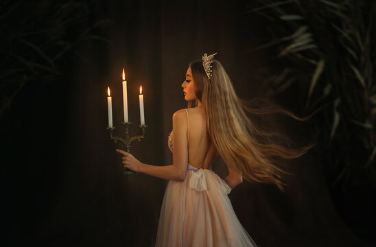 Fantasy medieval girl princess walks in dark gothic room. Woman queen is holding candlestick with burning candles in hand. Dress with open back, crown long loose blonde hair flying in motion. Go away