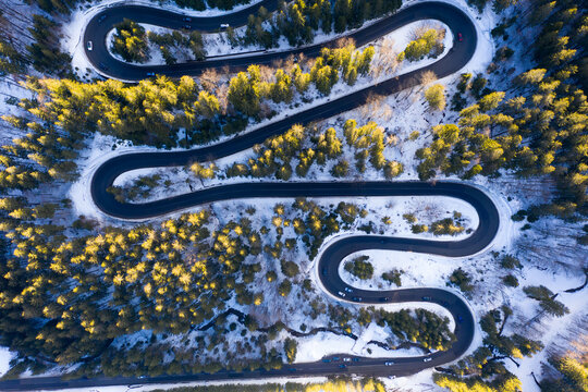 Aerial drone photograph bird's eye perspective of a beautiful winding mountain road in Romania in winter time