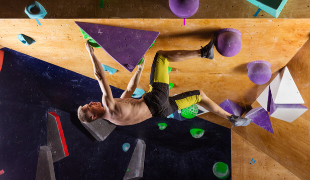 Young man bouldering in indoor climbing gym, trying to solve challenging problem