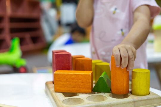 Focus on hands of little child girl playing with colorful wooden blocks in the room