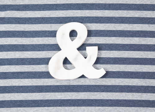 White Ampersand symbol on a striped background
