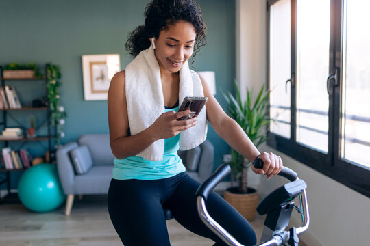 Afro young fitness girl using mobile phone while training on exercise bike at home.