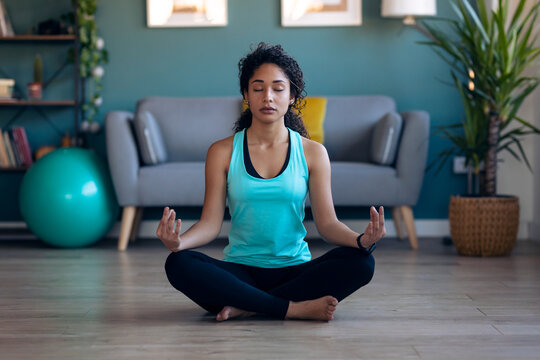African attractive sporty young woman doing yoga and hypopressive exercises while staying in lotus position in living room at home.