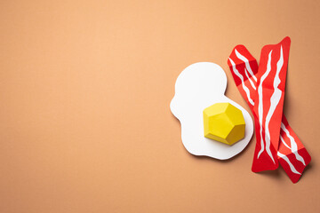 Paper craft food on beige or light brown background. Fried eggs and bacon slices cut from paper, top view. Creative breakfast or lunch flat lay concept, space for text template