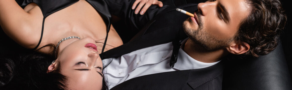 overhead view of elegant man with cigarette near sexy woman with closed eyes, banner