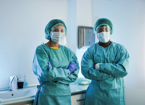 Multiracial medical workers wearing hazmat suit and protective face masks inside hospital laboratory