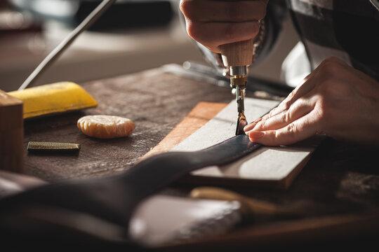Leather handbag craftsman at work in a vintage workshop. Small business concept