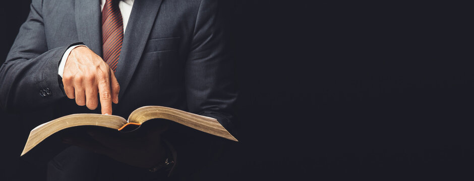 man in suit pointing a text on an open bible on a black background