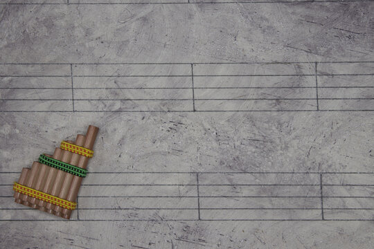 Music sheet background with a miniature instrument