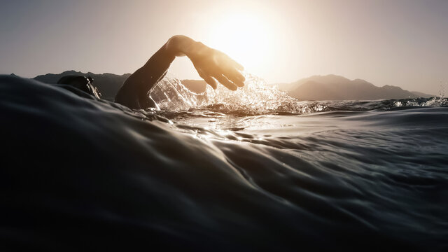 Athletic young man swimming at sea. Professional triathlon swimmer in ocean water. Young man athlete practicing at open water