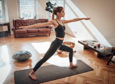 Dressed in black sportswear caucasian woman works out doing yoga staying on carpet with outstretched arms in shiny living room.