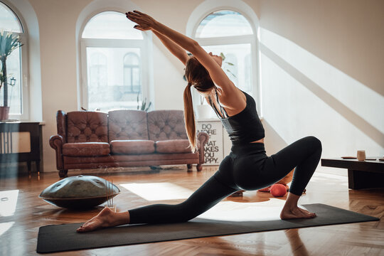 Atmospheric living room with sunbeams and relaxed sportswoman in black clothing works out doing yoga on carpet in Virabhadrasana posture.