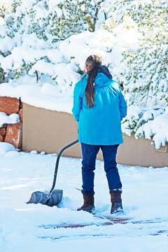 A woman shovels snow on a winter's day in Sedona, Arizona.