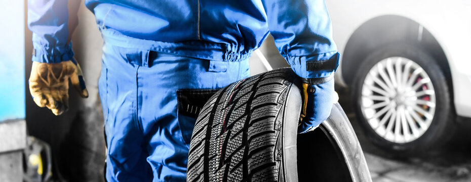 Mechanic holding tire with copy space for text repair service center, blurred background,
