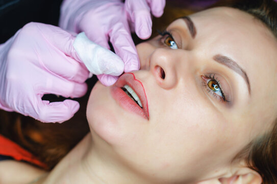 Carrying out the procedure of permanent lip make-up for a woman in a tattoo parlor.
