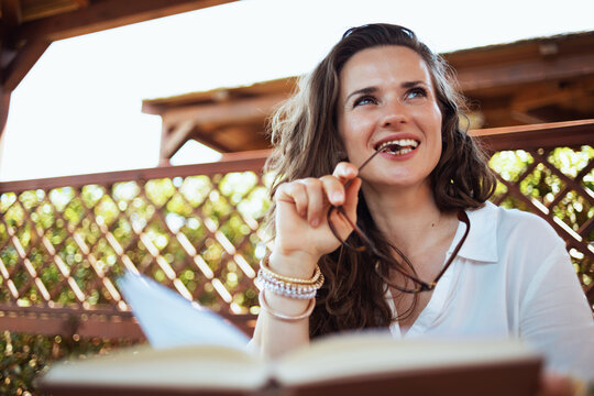 pensive stylish woman in white shirt with book and eyeglasses