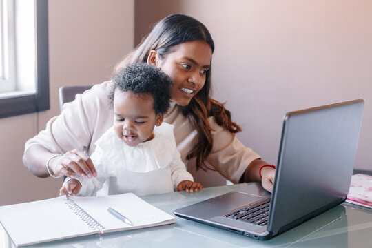 Mixed race Indian mother with African black baby working online from home on Internet. Workplace of freelancer woman with kid. Stay home single mom working distant job. A new normal.
