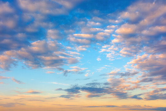 cloudscape in summer at sunrise. clouds on the blue sky in yellow and pink morning light. idyllic weather condition, picturesque scenery