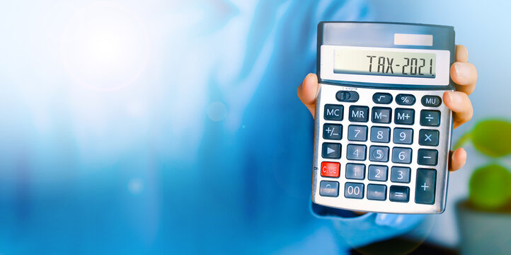 Man showing Tax word and  2021 number on calculator. Holding to count income and outcome. Business and tax concept. Pay tax in 2021 years.