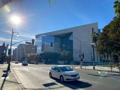 LOS ANGELES, CA, NOV 2020: wide view Los Angeles Police Department Headquarters in Downtown with traffic passing in foreground and sun with lens flares