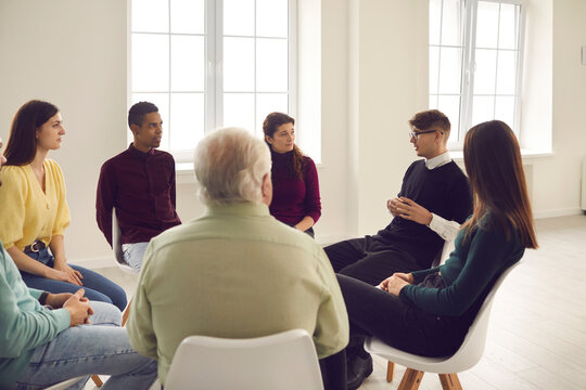 Diverse people listening to therapist sitting in circle in group therapy session. Patients talking, sharing concerns, coping with anxiety, dealing with psychological problems and insecurities together