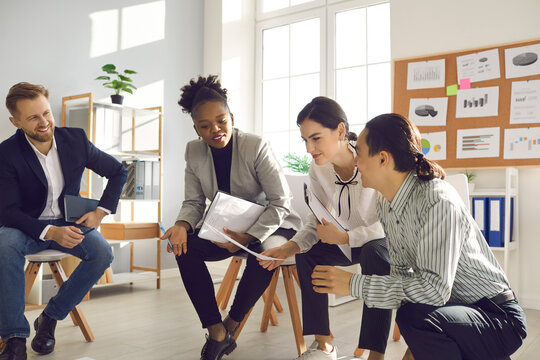 African woman talking to coworkers. Millennial business people working in office and thinking on project together. Female team manager, company owner, CEO or mentor suggesting ideas in group meeting