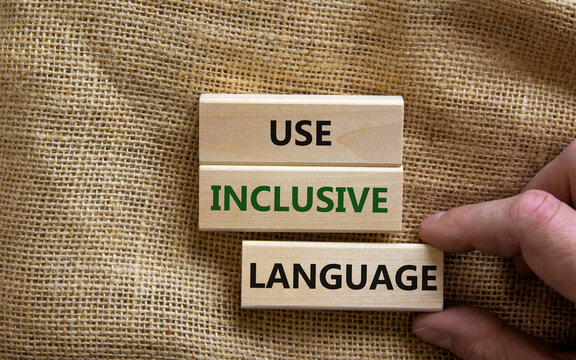 Use inclusive language symbol. Wooden blocks with words 'Use inclusive language'. Beautiful canvas background, businessman hand. Business and use inclusive language concept. Copy space.