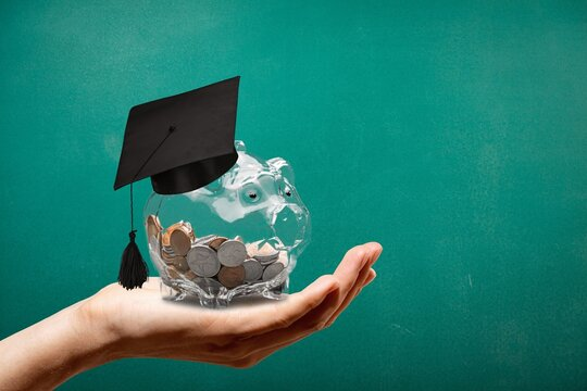 Graduation hat on a glass jar with money in hand