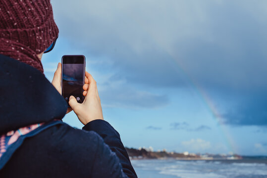 Back View man in warm clothes taking phone photo of rainbow view above the sea during a walk on winter seaside. Unity with nature, simple pleasures. Local self-traveling in autumn, winter. copy space.