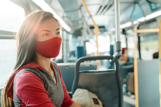 Woman wearing face mask inside public transport bus commuting to work. Asian girl passenger sitting with red facial fabric covering.