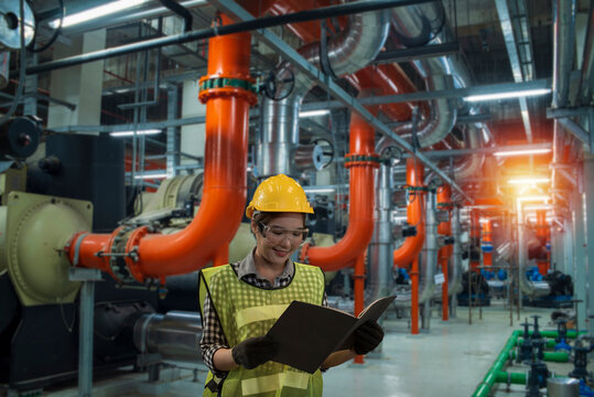 industrial workers at work. industrial plant in factory. women worker using  laptop on chiller water cool in plant room background.