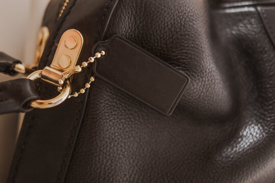Black tag on genuine pebble leather bag with gold furnitureBlack tag on genuine pebble leather bag with gold furniture. Fashion brand name mock up, closeup, top view, copy space for text