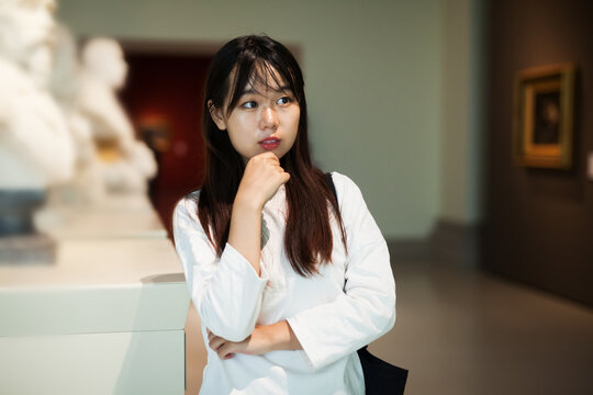 Attentive chinese girl with interest looking around at ancient sculptures in modern museum