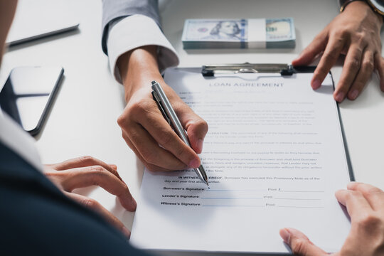 Businessman sign on money loan agreement contract to banker, loan and credit financial lease concept