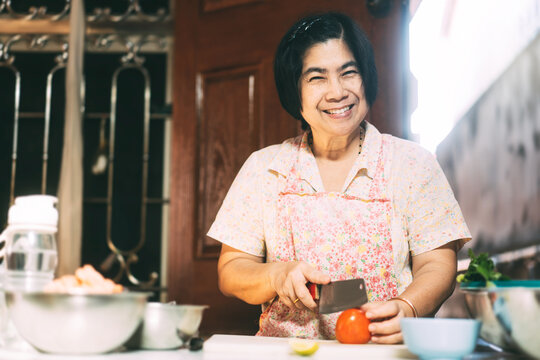 Aunthentic portrait of happy asian elderly woman cooking for family at local traditional kitchen style at home.
