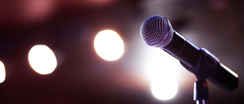 Close up of microphone on stage lighting at concert hall or conference room. copy space banner. soft focus.