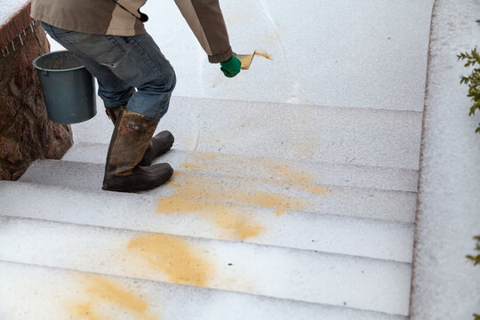 Hand sprinkles slippery steps with dry sand