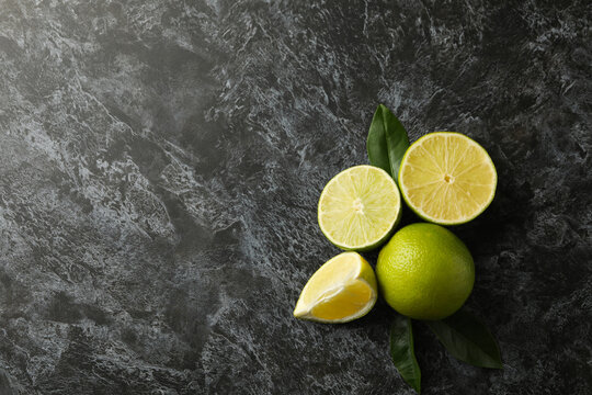 Ripe lime with leaves on black smokey background