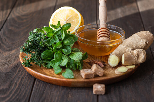 Mint, thyme, ginger root, lemon, honey and brown sugar on wooden plate. Ingredients for making ginger or herbal tea.
