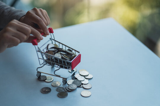 Hands holding a small shopping cart full of coins for saving money and financial concept