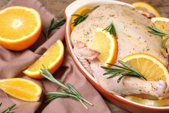 Chicken with orange slices and rosemary on table