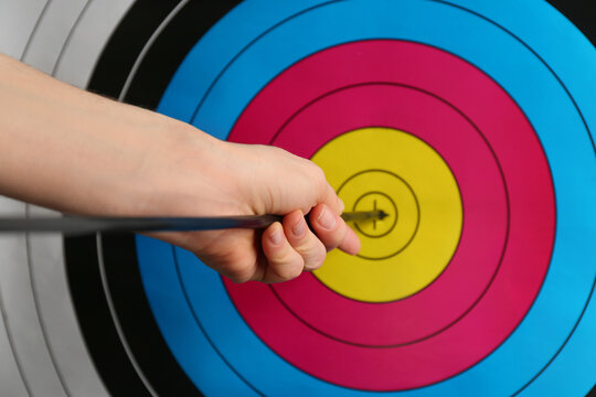 Woman pulling out arrow from archery target, closeup