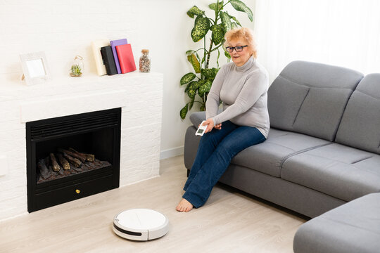 people, leisure, household and technology concept - elderly woman, robot vacuum cleaning floor at home