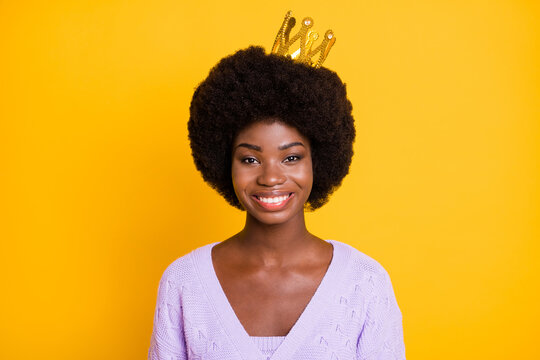 Portrait of charming dark skin lady gold crown on head beaming smile look camera isolated on yellow color background